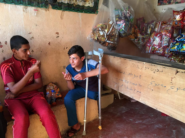 Mustafa and a friend hang out at a store near his house in Fallujah.