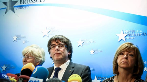 Catalonia's deposed leader, Carles Puigdemont (center), speaks at a news conference in Brussels on Tuesday with other members of his dismissed government.