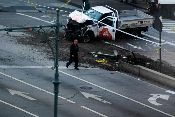 "An investigator walks past a crashed pickup truck following an attack in New York City.   The pickup's driver killed eight people on Tuesday, mowing down cyclists and pedestrians, before striking a school bus in what officials branded a ""cowardly act of terror."""
