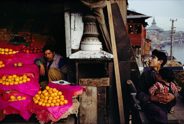 Fruit Seller and a boy with a child at Zaina Kadal Bridge, Jhelum River, Srinagar, Kashmir, 1979.