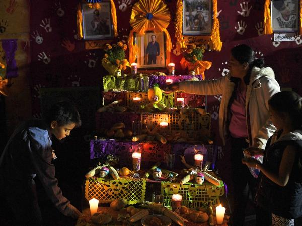 People gather in front of an altar in honor of the victims of Mexico's September 19 earthquake, in the site of a collapsed building at Tlalpan neighbourhood in Mexico City, on November 1, 2017.