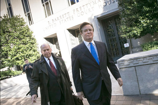 Former Trump campaign chairman Paul Manafort (right) leaves federal court after pleading not guilty following his indictment on federal charges Monday.