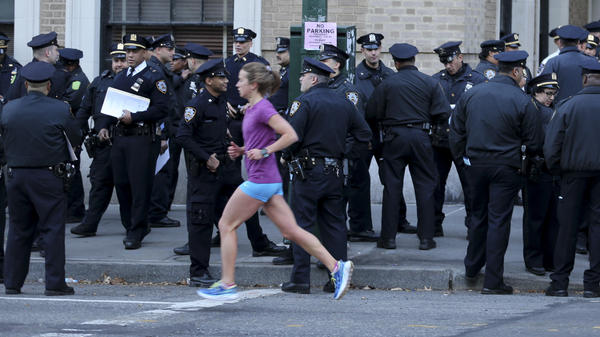 A runner moves past a group of police officers gathered near the finish line of the New York City Marathon on Nov. 6, 2016. Authorities are increasing the number of officers and other law enforcement personnel for this year's race, in the wake of Tuesday's terrorist attack in the city, in which a truck struck and killed eight bicyclists.