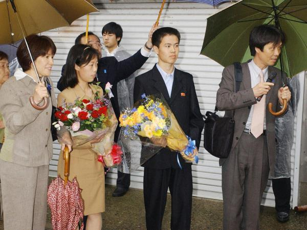 Former abductees Kaoru Hasuike (right) and his wife, Yukiko (left, holding umbrella), arrive at their home northwest of Tokyo with their two children (holding flowers) in 2004, after Japan won their release from North Korea.