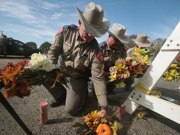 Police move flowers placed at a barricade near the First Baptist Church of Sutherland Springs on Monday in Sutherland Springs, Texas.