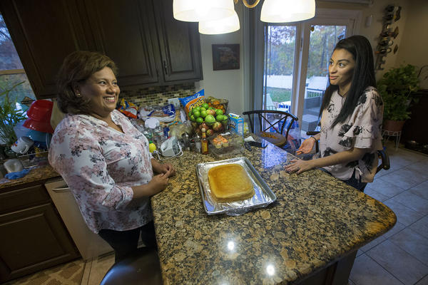 Irma Flores, right, and gher daughter Gabriela Portillo-Perez discuss how to proceed with making a tres leches cake as a surprise for Pertillo-Perez's husband. (Jesse Costa/WBUR)