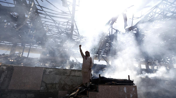 A Yemeni man stands at the site of an airstrike in the capital, Sanaa, on Sunday.