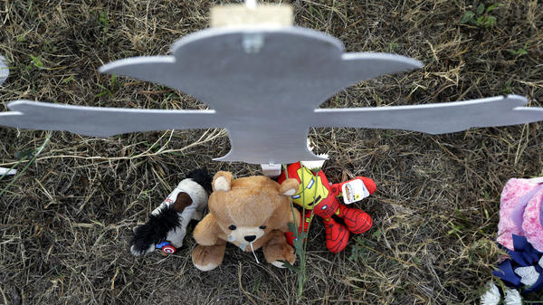Stuffed animals sit at the base of a cross at a makeshift memorial for victims in Sutherland Springs, Texas.