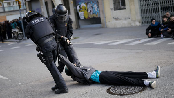 Regional police officers drag a protester from his post blocking a Barcelona street on Wednesday. The general strike, which blocked roads, highways and train tracks, ground much of Catalonia to a halt in support of the region's independence movement.