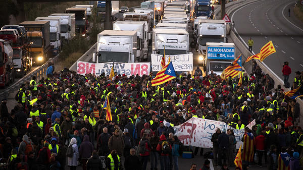 As part of a general strike Wednesday, protesters block a major highway in Borrassa, a municipality in Catalonia. The scene was just one of several miles-long traffic jams caused by demonstrators gathering on the region's streets and railways.