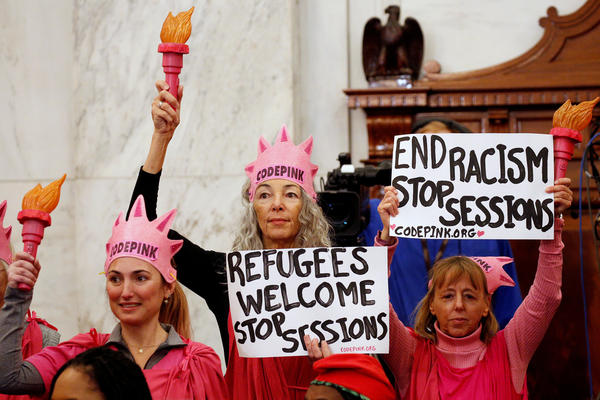 The government has dropped its case against Desiree Fairooz (center), who laughed out loud during Jeff Sessions' confirmation hearing in January.