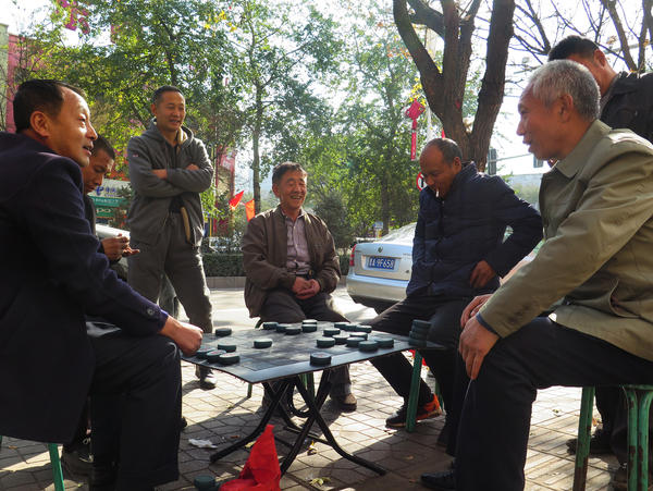 Men play Chinese chess on the sidewalk in the coal mining town of Gujiao.