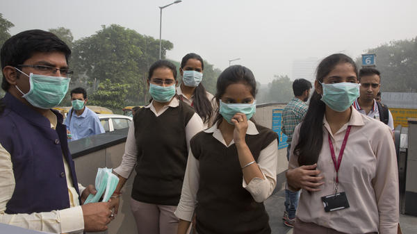 Volunteers distribute face masks in New Delhi on Thursday.