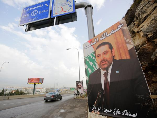 Lebanese Prime Minister Saad Hariri, who resigned last week in a televised speech from the Saudi capital, Riyadh, stares out from a poster on the side of a road in Tripoli, Lebanon.