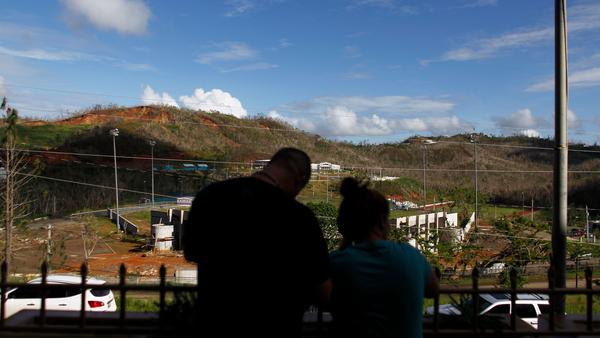 Two evacuees look out from the entrance of the Luis Muñoz Marín public school last week in Barranquitas, Puerto Rico. Many people from Barranquitas have been living in a shelter set up in the school since Hurricane Maria destroyed their homes in September.