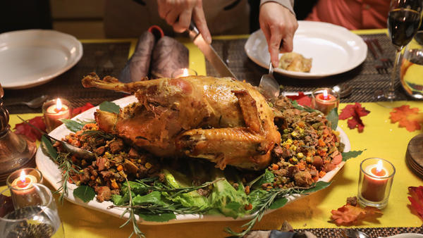 A Guatemalan immigrant family prepares for their Thanksgiving meal by cutting the turkey.