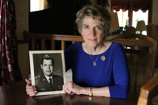 Jane Adams of Greeley, Colo., holds a photo of her first husband, Air Force pilot Mike Klingner