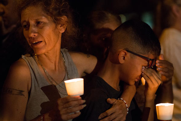 Mona Rodriguez holds her son J. Anthony Hernandez during a candlelight vigil held on Sunday night for the 26 people killed in a shooting at the First Baptist Church in Sutherland Springs.