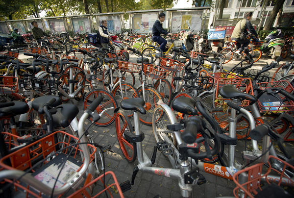 People ride bicycles and scooters past Mobike shared bicycles parked along a street in Beijing.