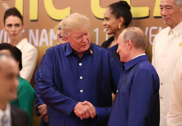 President Trump shakes hands with Russia's President Vladimir Putin as they pose for a group photo ahead of the Asia-Pacific Economic Cooperation (APEC) Summit leaders gala dinner in the central Vietnamese city of Danang on Nov. 10, 2017. (STR/AFP/Getty Images)