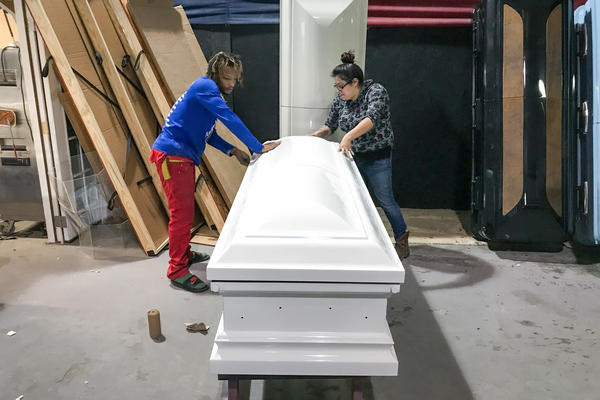 Kenneth Burnett and Maggie Rivera sand a casket, readying it for a pink camouflage paint job at the shop in Edna, Texas. The woman it is for loved to hunt.