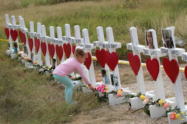 Four-year-old Shaelyn Gisler leaves a flower at a memorial where 26 crosses were placed to honor the 26 victims killed at the First Baptist Church of Sutherland Springs on November 9, 2017 in Sutherland Springs, Texas. On November 5, a gunman, Devin Patrick Kelley, shot and killed the 26 people and wounded 20 others when he opened fire during Sunday service at the church.