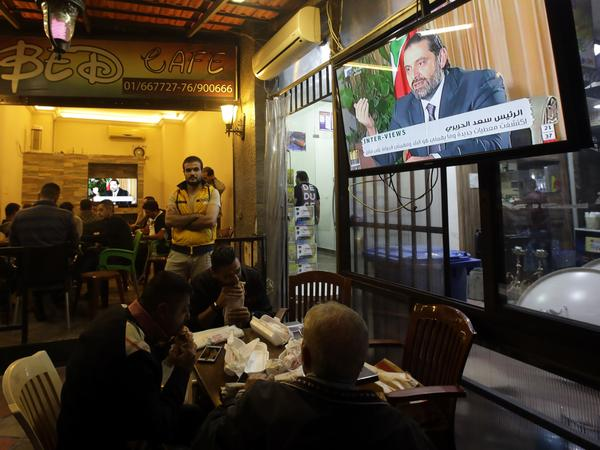 """People watch an interview with Saad Hariri, who resigned as prime minister Nov. 4, in a Beirut coffee shop on Sunday. Hariri pledged he would return to Lebanon from Saudi Arabia """"very soon"""" in his first television interview since his shock resignation."""