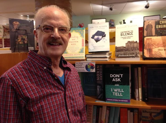 John Carroll Whitener stands with his new book, 'Don't Ask and I Will Tell' at Malaprops Bookstore.