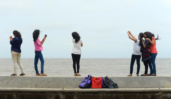In this photograph taken on June 15, 2015, young Indian students take 'selfies' on Marine Drive promenade in Mumbai.