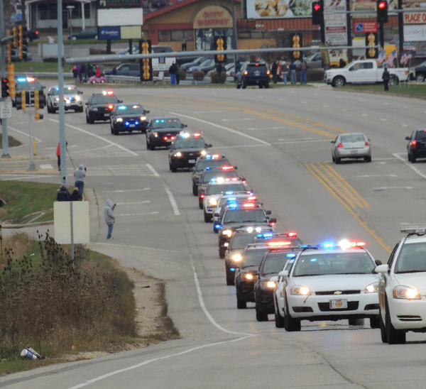 "A long line of police vehicles accompanies the body of fallen Rockford Police Officer Jaimie Cox on his traditional ""final tour"" Saturday."