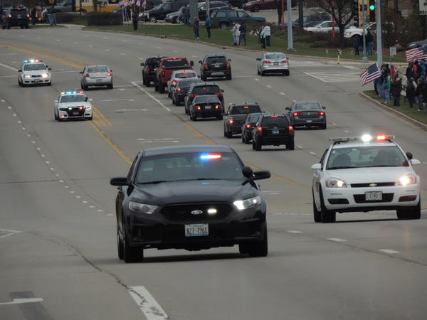 "Cars from many jurisdictions took part in the traditional ""last tour"" through Rockford following Saturday's funeral for Officer Jaimie Cox."
