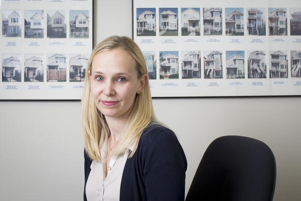Kristen Komara, vice president of financial wellness at the Resurrection Project, pictured at the Resurrection Project in Pilsen on Nov. 6, 2017, in Chicago. The houses pictured behind are of the first 140 homes built by the organization in the '90s that it then helped community members purchase. (Michelle Kanaar for Here & Now)