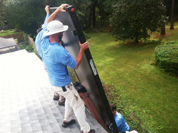 Workers install solar on Frank Moore's home in Temple Terrace