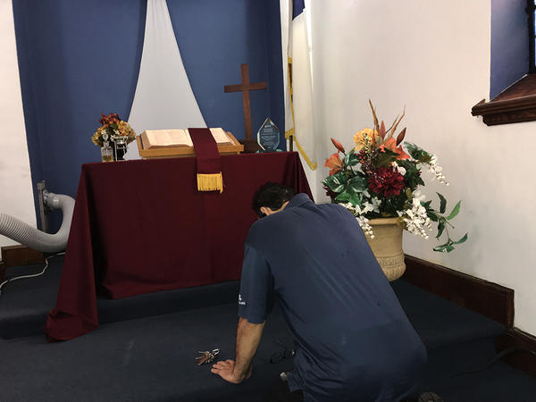 Nelson Robles demonstrates his prayer routine at Primera Iglesia Bautista Emanuel church in Bridgeport.