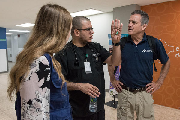 Dr. Rob Fuller, right, and Carrie Vopelak, left, hear about the state of the hospital's ER from Dr. Robles after Hurricane Maria. International Medical Corps is in Puerto Rico to assess the damage and help those suffering in the wake of the storm.