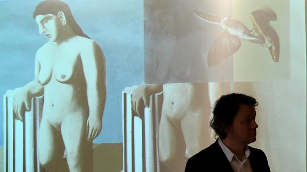 A man stands in front of a projection of the virtually recomposed painting <em>The Enchanted Pose</em> by René Magritte at The Royal Museums of Fine Arts of Belgium on Tuesday.
