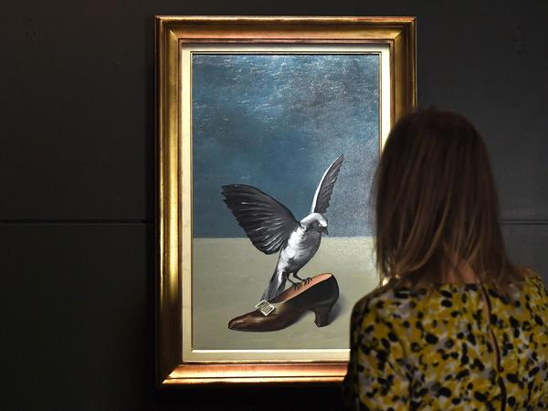 A woman looks at Magritte's <em>God is not a Saint,</em> which hides under its layers the missing and final piece of another Magritte work, <em>The Enchanted Pose,</em> at the Royal Museums of Fine Arts of Belgium in Brussels.