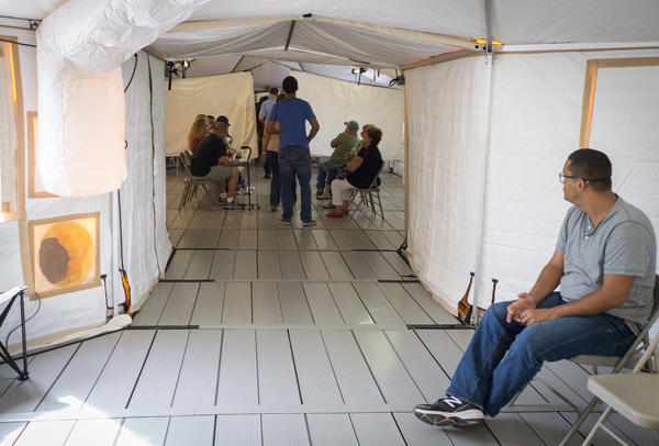 Patients wait for medical care at a temporary hospital tent outside the VA hospital in Ponce, Puerto Rico. The main building is unusable after Hurricane Maria.