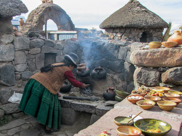 A Quechua woman tends to her clay oven in her outdoor kitchen on the road to the Sillustani archaeological site in Puno, Peru. The stone table is laid with a collection of potatoes and other tubers, as well as homemade cheese and bread.