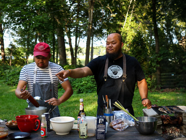 """Chris Her (left) and Yia Vang prepare Hmong style food. """"Every dish has a narrative,"""" Vang says, """"and if you follow that narrative closely enough, you understand the people."""""""