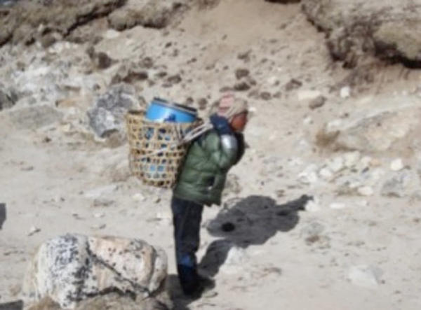 <p>A porter carries a barrel of human waste from Mount Everest base camp to the small village of Gorak Shep.</p>