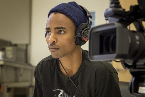 Filmmaker Abdirahman Abdi conducting an interview for his film at UMass. (Robin Lubbock/WBUR)