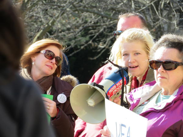 AFSCME spokeswoman Sara Dorner (right) addresses the crowd during a protest Monday in front of NIU's Altgeld Hall.