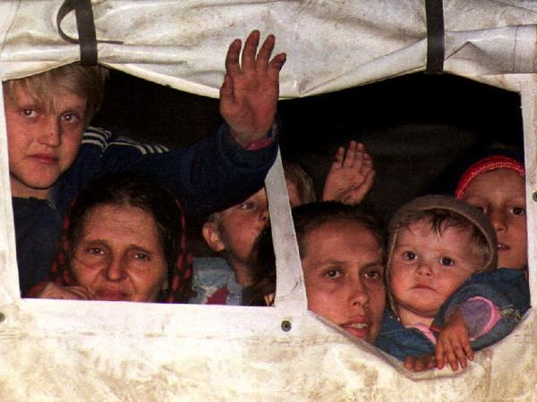 Bosnian refugees peer out from a U.N. truck in March 1993 after being evacuated from Srebrenica.