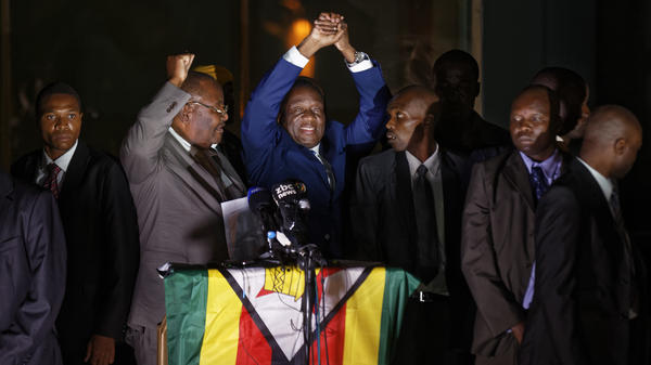 Emmerson Mnangagwa, center, greets supporters gathered outside the ZANU-PF party headquarters in downtown Harare, Zimbabwe on Wednesday.