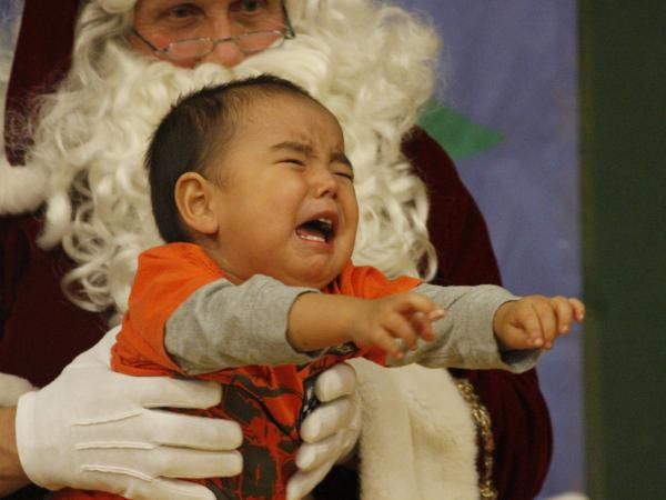 A crying child unsure of what to make of Santa Claus in Shishmaref, Alaska.