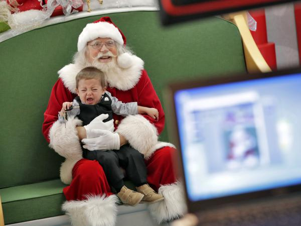 An unhappy child has his photo taken with Santa at the Chandler Mall, in Chandler, Ariz.