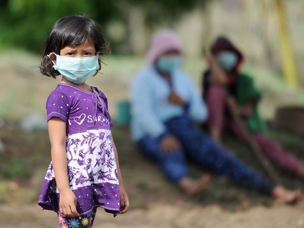 A Balinese girl wears a mask as as Mount Agung erupts in Kubu sub-district in Karangasem Regency, on Indonesia's resort island of Bali on Monday.