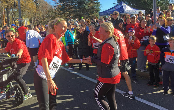 Shalane Flanagan greets finishers at the Back The Track 5K in Marblehead, Mass. (Alex Ashlock/Here & Now)
