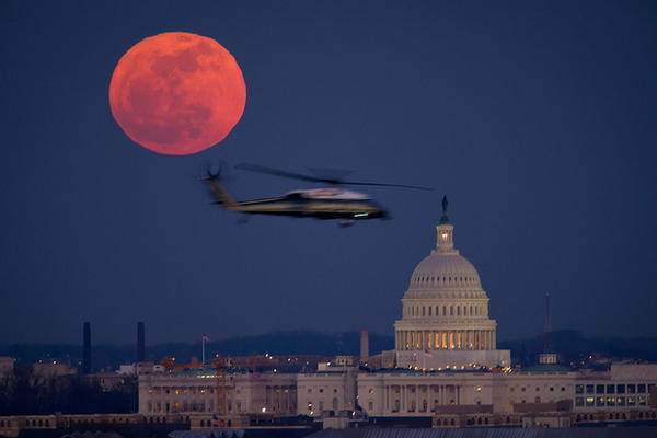 A U.S. Marine Corps helicopter flies through NASA photographer Bill Ingalls' supermoon composition in 2012.
